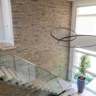 Große Moderne Holztreppe in L-Form mit offenen Setzstufen, Glasgeländer und Ziegelwänden in Toronto