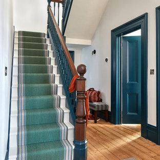 Immagine di un ingresso o corridoio minimal di medie dimensioni con pareti bianche, moquette e pavimento verde