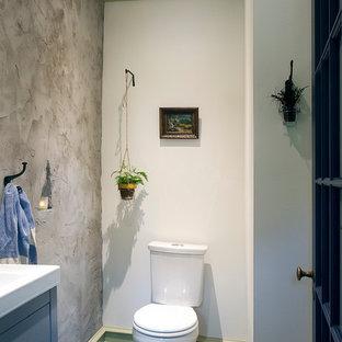 Foto de cuarto de baño ecléctico, pequeño, con armarios con paneles lisos, puertas de armario grises, sanitario de dos piezas, paredes grises, suelo de pizarra, lavabo suspendido y suelo verde