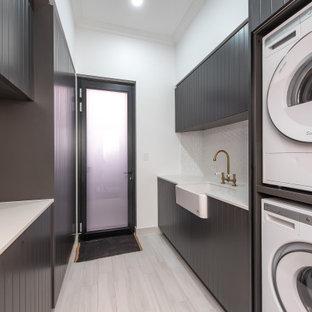 Inredning av en modern vita parallell vitt tvättstuga enbart för tvätt, med en rustik diskho, svarta skåp, bänkskiva i koppar, vitt stänkskydd, stänkskydd i mosaik, vita väggar, klinkergolv i porslin, en tvättpelare och grått golv