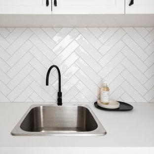 Idéer för en stor modern vita linjär tvättstuga, med en nedsänkt diskho, luckor med upphöjd panel, vita skåp, bänkskiva i kvarts, vitt stänkskydd, stänkskydd i stickkakel, mellanmörkt trägolv och brunt golv