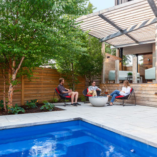 Inspiration for a modern partial sun backyard concrete paver and wood fence landscaping in Toronto for summer.