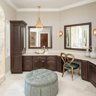 Inspiration for a large traditional master bathroom in Phoenix with raised-panel cabinets, dark wood cabinets, an undermount tub, a curbless shower, a bidet, beige tile, stone slab, beige walls, marble floors, a vessel sink, marble benchtops, beige floor, a hinged shower door, beige benchtops, a shower seat, a double vanity, a built-in vanity and wallpaper.