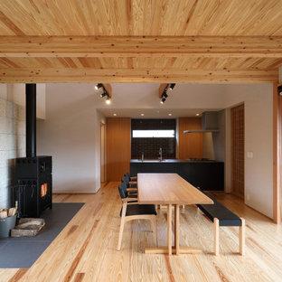 他の地域の広いアジアンスタイルのおしゃれなLDK (ベージュの壁、塗装フローリング、薪ストーブ、石材の暖炉まわり、ベージュの床、表し梁、ベージュの天井) の写真