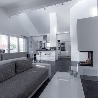 Idee per un ampio soggiorno design aperto con pareti bianche, pavimento in linoleum, stufa a legna, cornice del camino in intonaco, pavimento grigio, sala formale e TV a parete