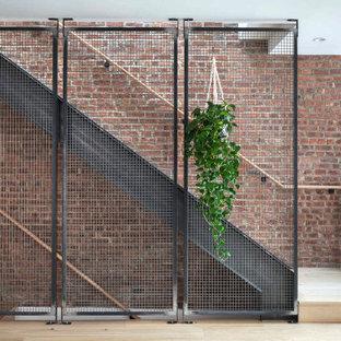 Immagine di una scala a rampa dritta minimalista di medie dimensioni con pedata in legno, nessuna alzata, parapetto in metallo e pareti in mattoni