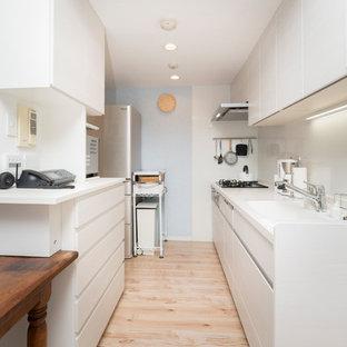 東京23区の北欧スタイルのおしゃれなII型キッチン (一体型シンク、フラットパネル扉のキャビネット、白いキャビネット、白いキッチンパネル、淡色無垢フローリング、茶色い床) の写真