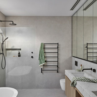 Photo of a mid-sized contemporary master bathroom in Melbourne with marble benchtops, grey floor, white benchtops, a built-in vanity, a freestanding tub, a curbless shower, a wall-mount toilet, gray tile, stone tile, grey walls, an undermount sink, an open shower and a double vanity.