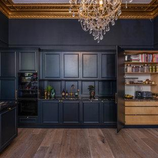 サセックスの広いトラディショナルスタイルのおしゃれなキッチン (ドロップインシンク、インセット扉のキャビネット、青いキャビネット、御影石カウンター、青いキッチンパネル、木材のキッチンパネル、黒い調理設備、淡色無垢フローリング、茶色い床、黒いキッチンカウンター、格子天井) の写真