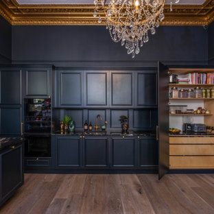 Inspiration for a large traditional single-wall eat-in kitchen in Sussex with a drop-in sink, beaded inset cabinets, blue cabinets, granite benchtops, blue splashback, timber splashback, black appliances, light hardwood floors, with island, brown floor, black benchtop and coffered.