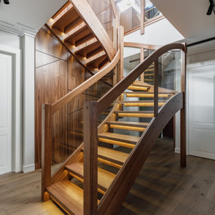 Идея дизайна: изогнутая лестница в современном стиле с деревянными ступенями и перилами из смешанных материалов без подступенок