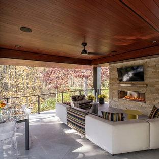 Immagine di un portico minimal di medie dimensioni e dietro casa con un caminetto, piastrelle, un tetto a sbalzo e parapetto in cavi