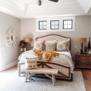 Diseño de dormitorio machihembrado y abovedado con paredes grises, suelo de madera en tonos medios y suelo marrón