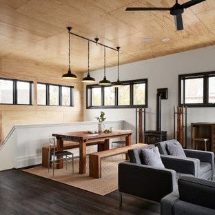 Immagine di una sala da pranzo industriale con pareti bianche, pavimento in vinile, stufa a legna, pavimento grigio, soffitto in legno e pareti in legno