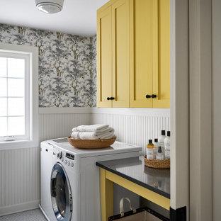 Bild på en mellanstor lantlig svarta parallell svart tvättstuga enbart för tvätt, med skåp i shakerstil, gula skåp, bänkskiva i kvarts, beige stänkskydd, beige väggar, klinkergolv i keramik, en tvättmaskin och torktumlare bredvid varandra och vitt golv
