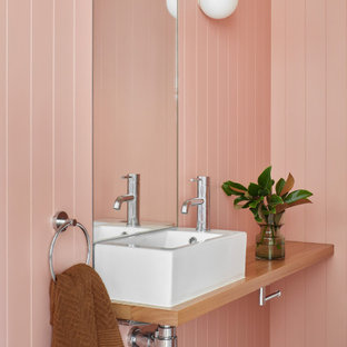 Mid-sized contemporary bathroom in Melbourne with medium wood cabinets, pink walls, a pedestal sink, wood benchtops, brown benchtops, a single vanity, a floating vanity and panelled walls.