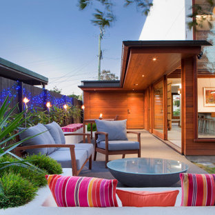 Photo of a mid-sized contemporary backyard patio in Brisbane with a fire feature, gravel and an awning.