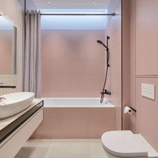 На фото: маленькая главная ванная комната в современном стиле с плоскими фасадами, белыми фасадами, ванной в нише, инсталляцией, розовой плиткой, керамогранитной плиткой, серыми стенами, полом из керамогранита, накладной раковиной, столешницей из плитки, серым полом, серой столешницей, нишей, тумбой под одну раковину, подвесной тумбой и многоуровневым потолком