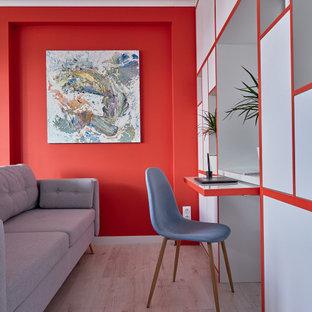 Immagine di uno studio design con pareti rosse, parquet chiaro, scrivania incassata e pavimento beige