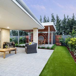 Modelo de terraza actual, de tamaño medio, en patio trasero y anexo de casas