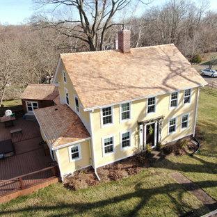 Geräumiges, Dreistöckiges, Gelbes, Rotes Country Einfamilienhaus mit Holzfassade, Satteldach, Schindeldach und Verschalung in Bridgeport