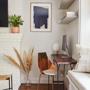 Идея дизайна: маленький кабинет в стиле неоклассика (современная классика) с белыми стенами, паркетным полом среднего тона, стандартным камином, фасадом камина из кирпича и отдельно стоящим рабочим столом