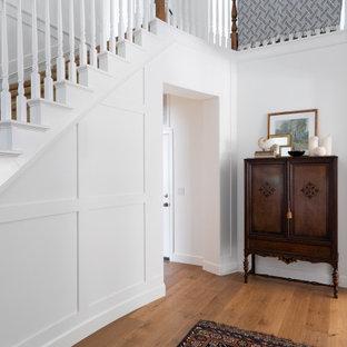 サンディエゴの中くらいのトラディショナルスタイルのおしゃれな玄関ロビー (白い壁、無垢フローリング、茶色い床、パネル壁) の写真