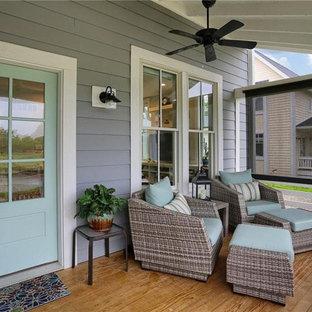 Ispirazione per un grande portico stile americano davanti casa con pedane, un tetto a sbalzo e parapetto in legno