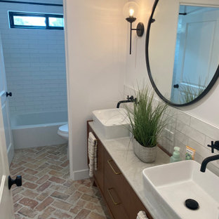Mid-sized transitional kids bathroom in Los Angeles with flat-panel cabinets, medium wood cabinets, an alcove tub, a shower/bathtub combo, a one-piece toilet, white tile, ceramic tile, white walls, brick floors, a vessel sink, granite benchtops, red floor, a shower curtain, white benchtops, a double vanity and a freestanding vanity.