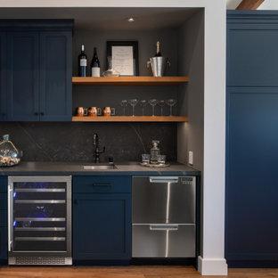 サンフランシスコの広いトランジショナルスタイルのおしゃれなウェット バー (I型、ドロップインシンク、レイズドパネル扉のキャビネット、青いキャビネット、御影石カウンター、グレーのキッチンパネル、御影石のキッチンパネル、淡色無垢フローリング、茶色い床、グレーのキッチンカウンター) の写真