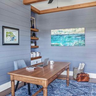 Mittelgroßes Maritimes Arbeitszimmer ohne Kamin mit Arbeitsplatz, blauer Wandfarbe, braunem Holzboden, freistehendem Schreibtisch, braunem Boden, freigelegten Dachbalken und Holzdielenwänden in Austin