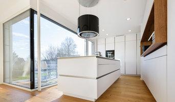 Weiße Wohnküche mit Holzakzenten direkt am Balkon