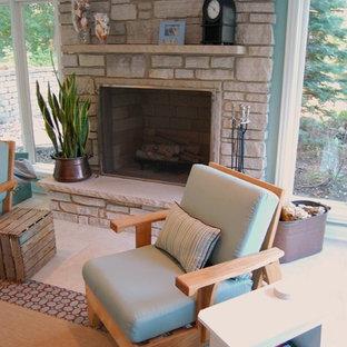 シカゴの中サイズのエクレクティックスタイルのおしゃれなファミリールーム (青い壁、セラミックタイルの床、標準型暖炉、石材の暖炉まわり、ベージュの床) の写真