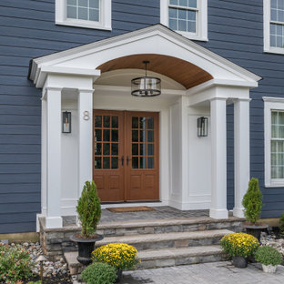 Идея дизайна: большая входная дверь с синими стенами, бетонным полом, двустворчатой входной дверью, входной дверью из дерева среднего тона, бежевым полом, деревянным потолком и панелями на части стены