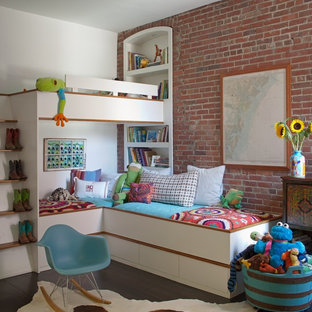 This is an example of an industrial gender-neutral kids' bedroom for kids 4-10 years old in Atlanta with dark hardwood floors and red walls.