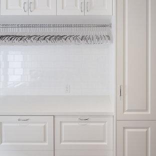 Immagine di una grande sala lavanderia classica con lavello sottopiano, ante con bugna sagomata, ante bianche, top in superficie solida, pavimento in laminato, lavatrice e asciugatrice affiancate, pavimento beige e pareti bianche