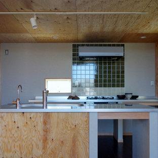 他の地域の中くらいのコンテンポラリースタイルのおしゃれなキッチン (一体型シンク、ステンレスカウンター、緑のキッチンパネル、磁器タイルのキッチンパネル、シルバーの調理設備、合板フローリング、茶色い床、グレーのキッチンカウンター、板張り天井) の写真