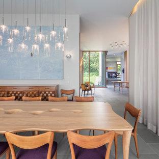 Foto på en stor funkis separat matplats, med vita väggar, kalkstensgolv och blått golv