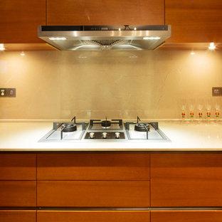 Immagine di una cucina contemporanea di medie dimensioni con ante lisce, ante in legno scuro, top in pietra calcarea, paraspruzzi beige, paraspruzzi in lastra di pietra e elettrodomestici in acciaio inossidabile