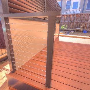 Foto di un grande patio o portico moderno dietro casa con pedane e una pergola