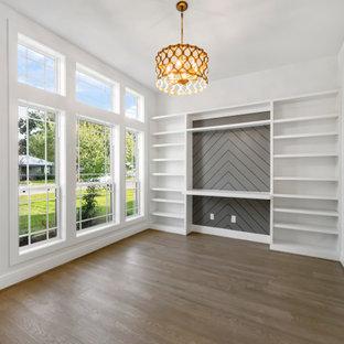 Klassisches Arbeitszimmer mit Arbeitsplatz, weißer Wandfarbe, hellem Holzboden, Einbau-Schreibtisch und Holzdielenwänden in Houston
