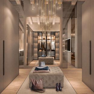Bild på ett mycket stort funkis walk-in-closet, med luckor med glaspanel, skåp i ljust trä och ljust trägolv