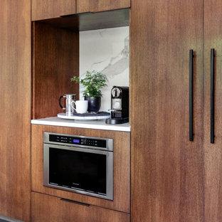 Modern inredning av ett avskilt, litet vit linjärt vitt kök, med släta luckor, skåp i mellenmörkt trä, bänkskiva i kvarts, vitt stänkskydd, glaspanel som stänkskydd, rostfria vitvaror, klinkergolv i porslin och svart golv