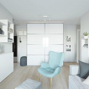 Immagine di un piccolo soggiorno nordico aperto con pareti grigie, pavimento in laminato, TV a parete e pavimento rosa