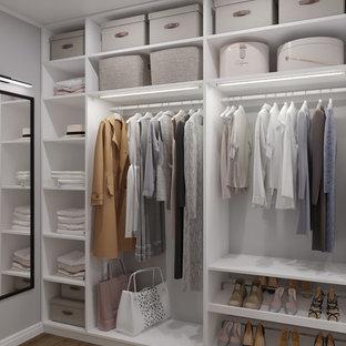 Imagen de armario vestidor unisex, nórdico, pequeño, con armarios abiertos, puertas de armario blancas, suelo marrón y suelo de madera en tonos medios
