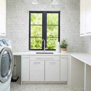 Idéer för en stor klassisk vita u-formad tvättstuga enbart för tvätt, med en undermonterad diskho, släta luckor, vita skåp, bänkskiva i kvarts, vitt stänkskydd, stänkskydd i terrakottakakel, vita väggar, marmorgolv, en tvättmaskin och torktumlare bredvid varandra och vitt golv
