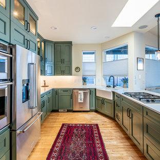 Стильный дизайн: кухня в стиле неоклассика (современная классика) с раковиной в стиле кантри, зелеными фасадами, белым фартуком, техникой из нержавеющей стали, паркетным полом среднего тона, островом, оранжевым полом и белой столешницей - последний тренд