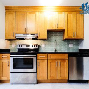 Exemple d'une petite cuisine américaine moderne en L avec un évier encastré, un placard à porte shaker, des portes de placard en bois brun, un plan de travail en granite, une crédence verte, une crédence en carreau de verre, un électroménager en acier inoxydable, un sol en carrelage de céramique, aucun îlot, un sol gris et un plan de travail noir.