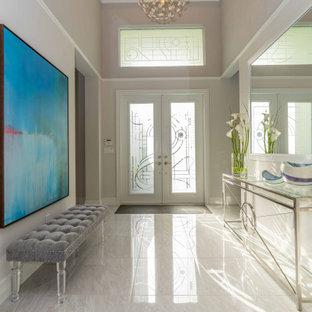 Foto de distribuidor casetón, tradicional renovado, de tamaño medio, con paredes beige, suelo de mármol, puerta doble, puerta de vidrio y suelo beige