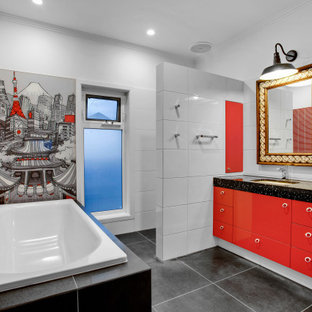 This is an example of a large eclectic master bathroom in Melbourne with flat-panel cabinets, red cabinets, a drop-in tub, an alcove shower, a one-piece toilet, white tile, porcelain tile, red walls, ceramic floors, an undermount sink, engineered quartz benchtops, black floor, an open shower, black benchtops, a niche, a single vanity and a built-in vanity.